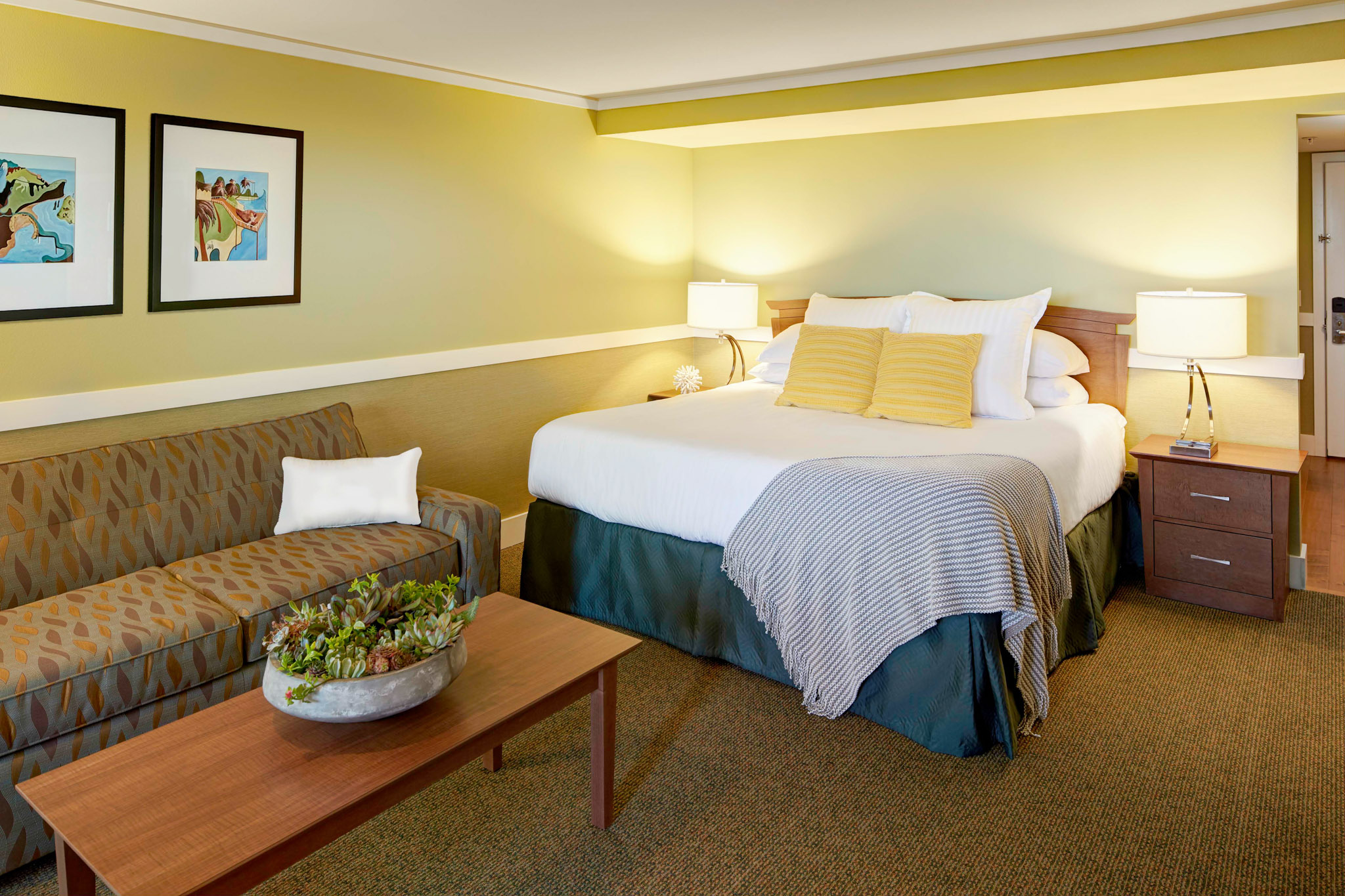 king bed and couch inside beachfront hotel room with patio in cannon beach